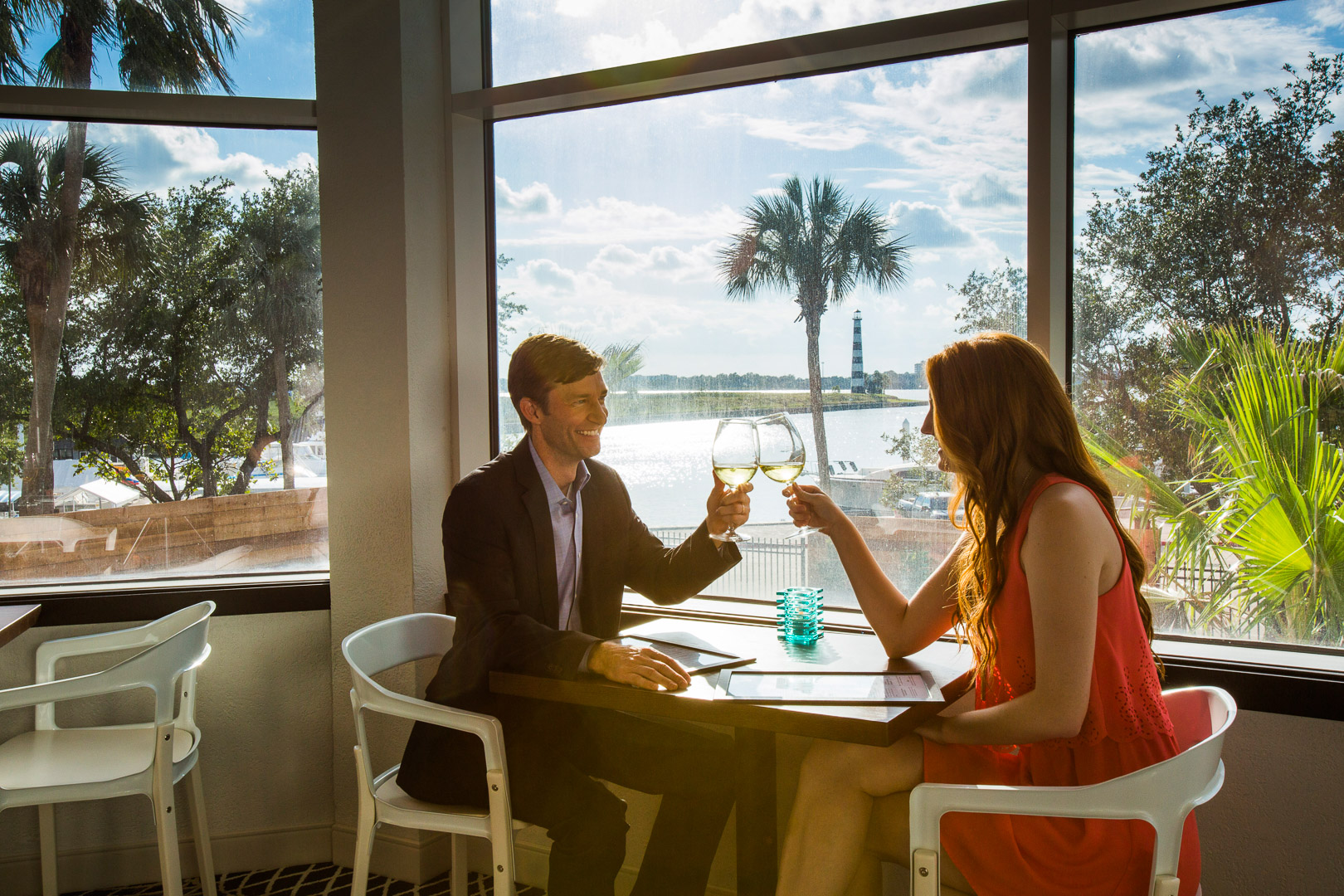 couple clinking their wine glasses at a restaurant with a beach view