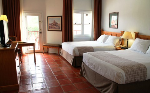 double queen beds on rust colored tile floors