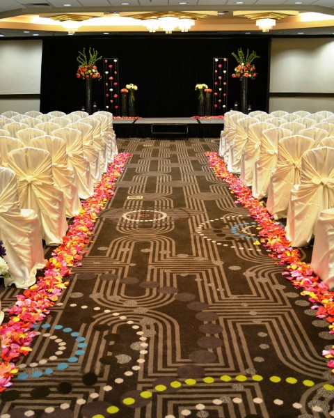 rows of chairs draped in ivory fabric and an aisle lined with flower petals