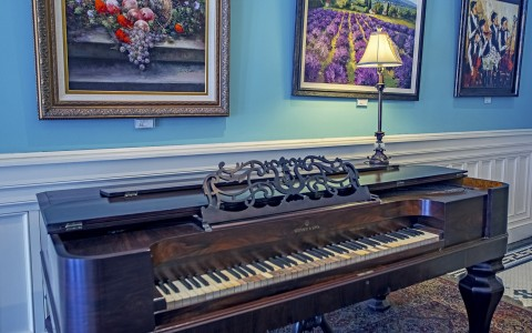 wooden piano by wall with paintings of flowers hanging on it