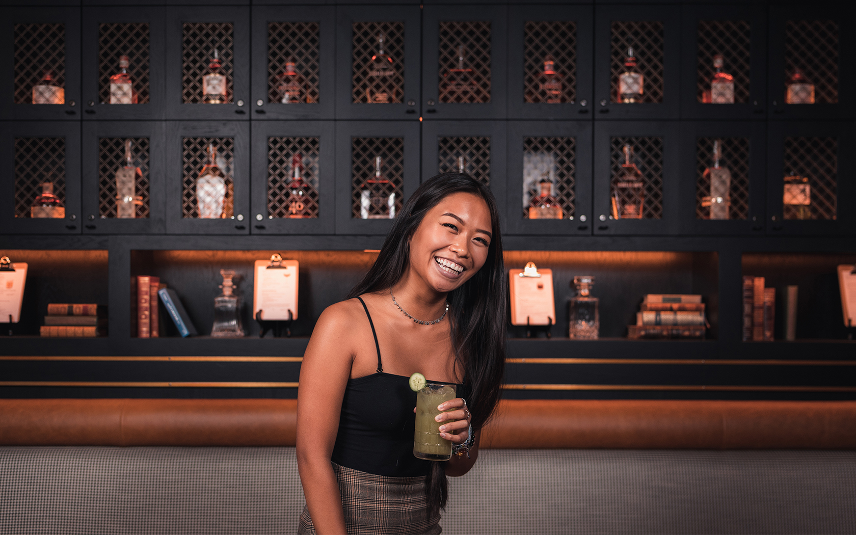 woman smiling in front of wall with whiskey bottles