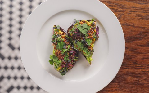 Avocado toast on rustic bread with spiced seeds and mint leaves
