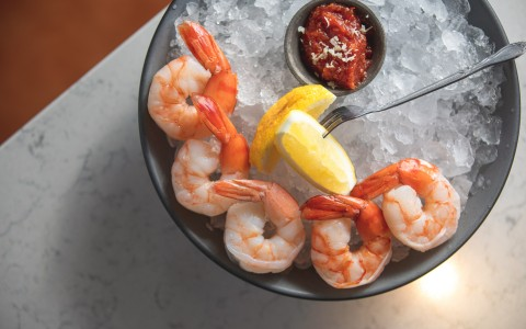 Shrimp cocktail bowl with ice and sliced lemons