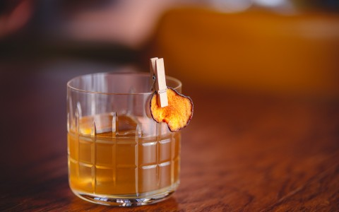 Glass of bourbon with a dried up orange peel
