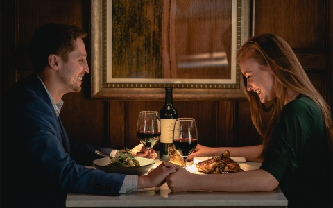 couple holding hands on intimate date night with wine
