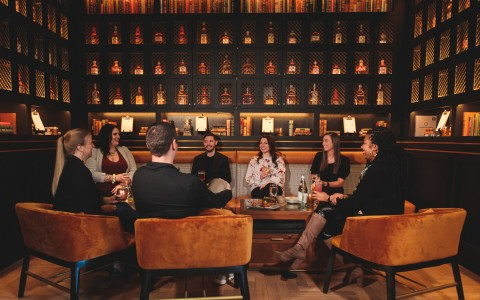 Group of people sitting around with cocktails in the Whiskey Room
