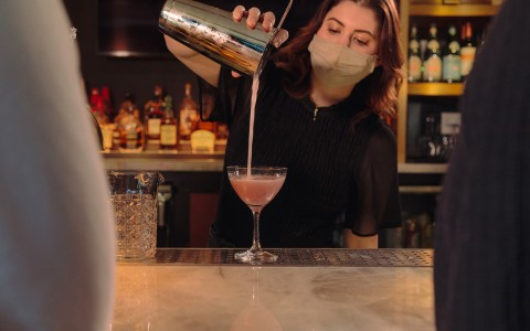 Female bartender wearing face mask pouring a cocktail