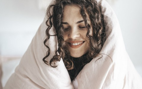 woman laughing under covers.