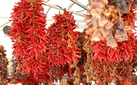 dried red chillies hanging on a market place