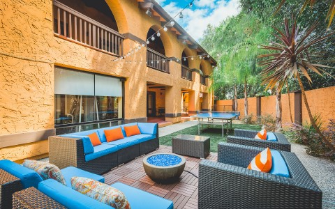 outside lounge area with blue couches and firepit