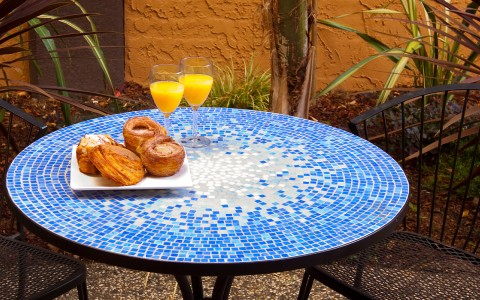 blue patio table with breakfast pastries on a plate