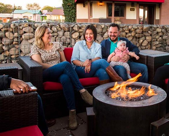family smiling sitting in an outdoor patio near a fire pit