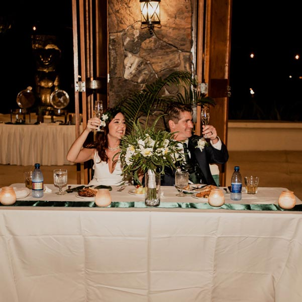 bride and groom sitting and raising their drinks