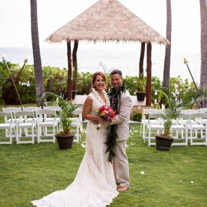 posing with wedding dress and suit and hawaiian leis