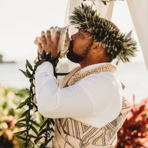a man drinking from a coconut during his wedding