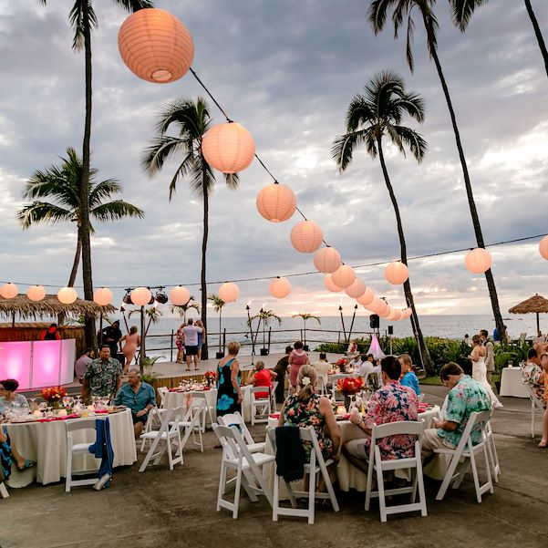 wedding reception outside with tall palm trees and lanterns