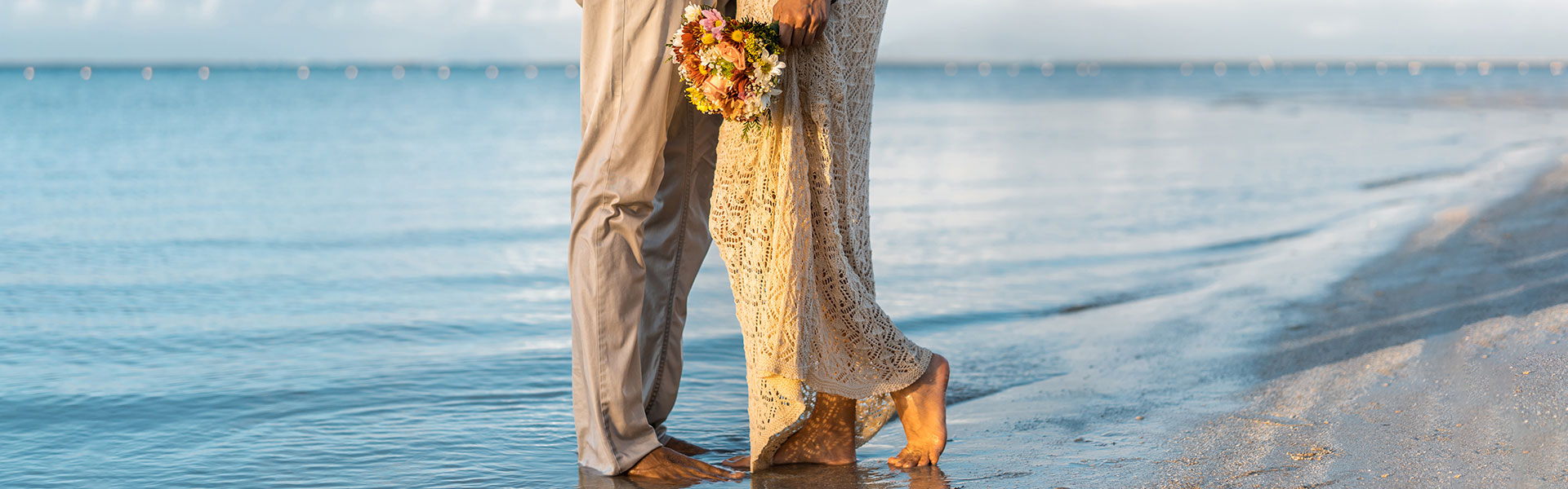 couple standing on the beach with feet in the water
