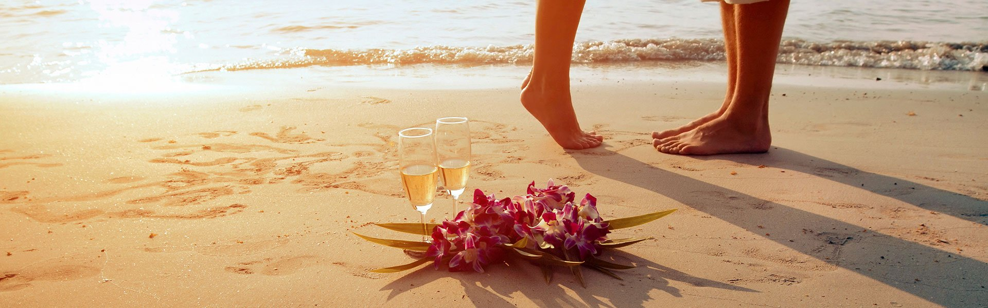 feet shot with champagne glasses on the sand next to them