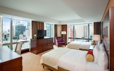 large hotel room with two big beds, a television, and a view of the city