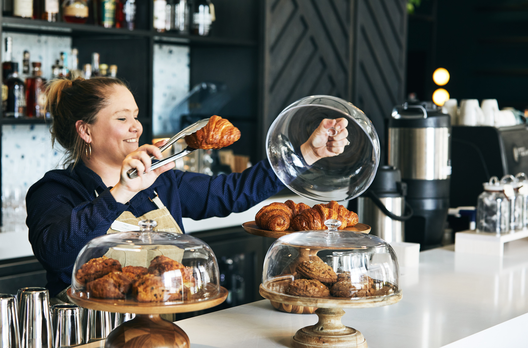 woman holding croissant at coffee bar
