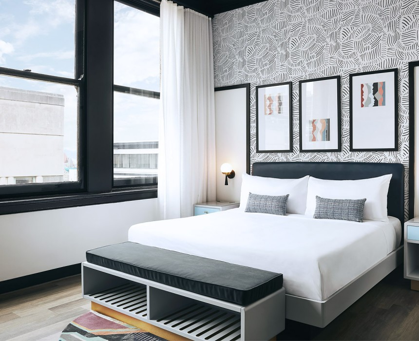 airy hotel room with bright windows and black and white wallpaper headboard