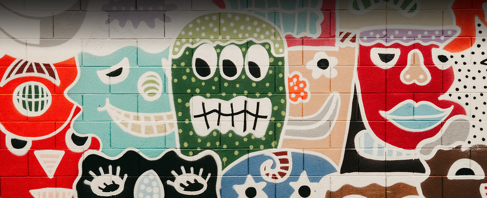 mural with collage of funky smiling faces of all colors