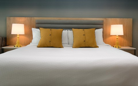 a king bed with orange pillows