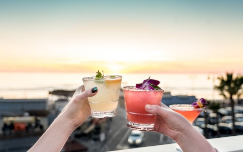a couple drinking cocktails on the beach