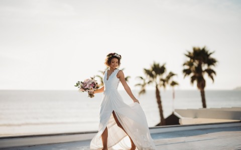 a woman on the beach in a wedding dress