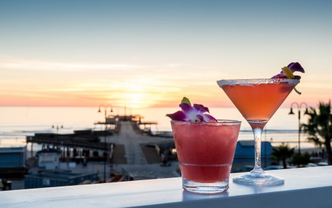 2 craft cocktails with view of pier