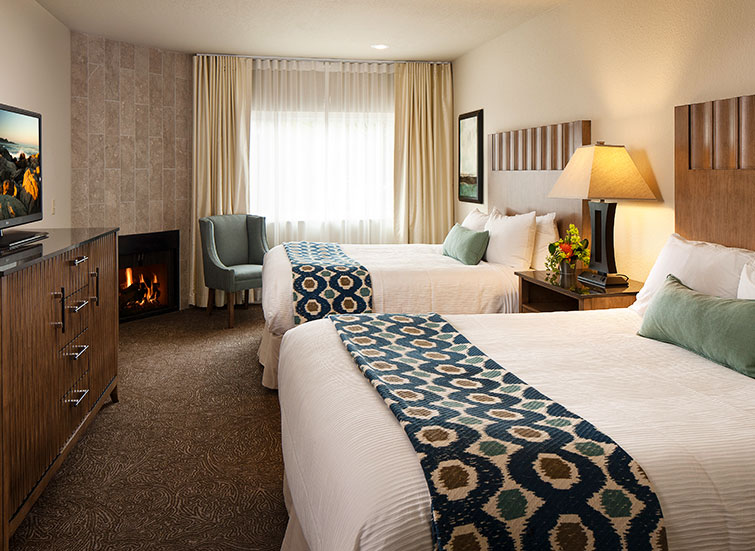 hotel room with 2 beds and a fireplace