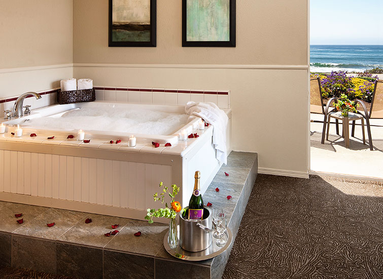hot tub lined with rose petals and champagne bottle