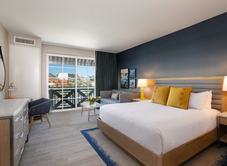 a guest suite with king bed and yellow pillows
