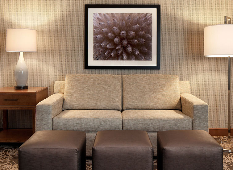 couch with three brown feet rests and framed art on wall