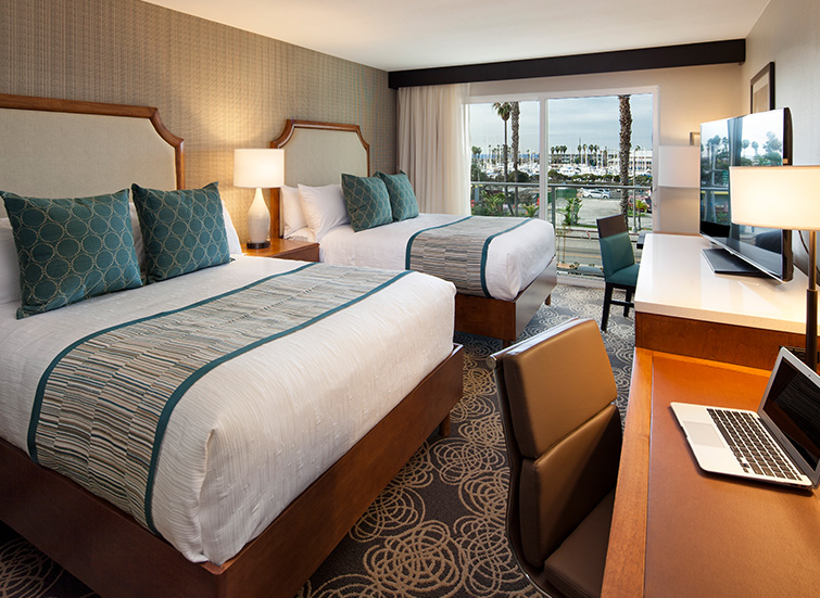 two large hotel beds with bright window overlooking the marina