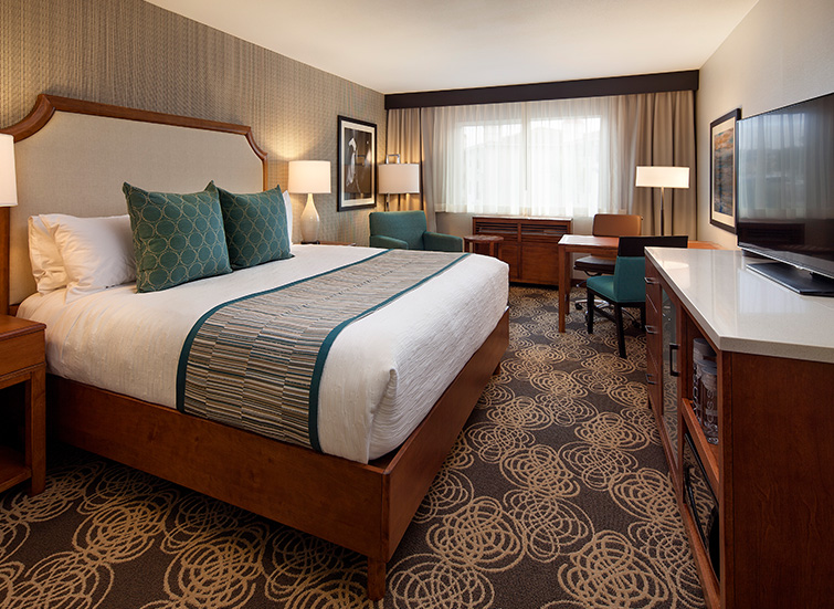 large hotel bed with work desk and multiple teal chairs