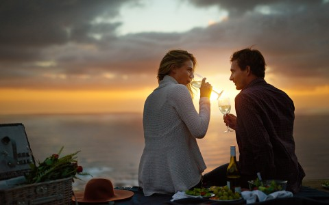 couple drinking on the beach at sundown
