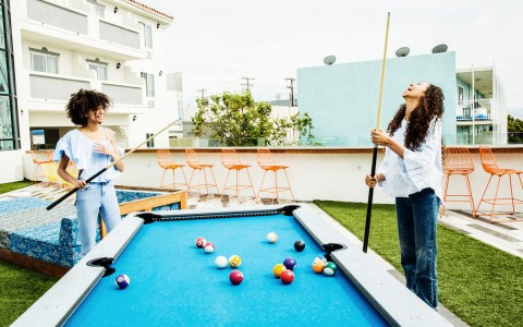 women playing pool and laughing