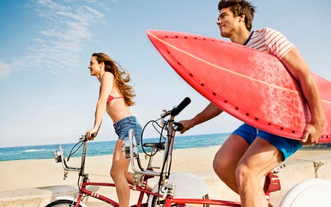 couple siding bikes next to the beach with a surfboard