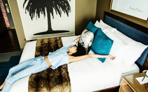 Woman stretching on hotel bed