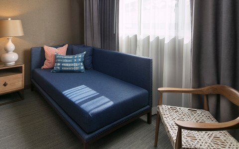 navy blue day bed with decorative pillows