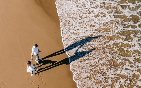 Overhead image of couple walking towards ocean