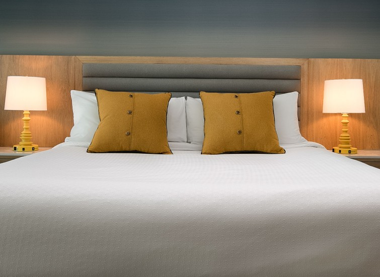 a king bed with four orange pillows