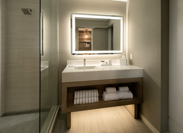 a guest bathroom with a shower and vanity