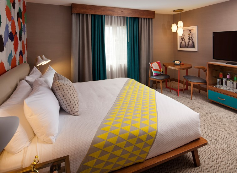 Hotel bed with a yellow decorative blanket