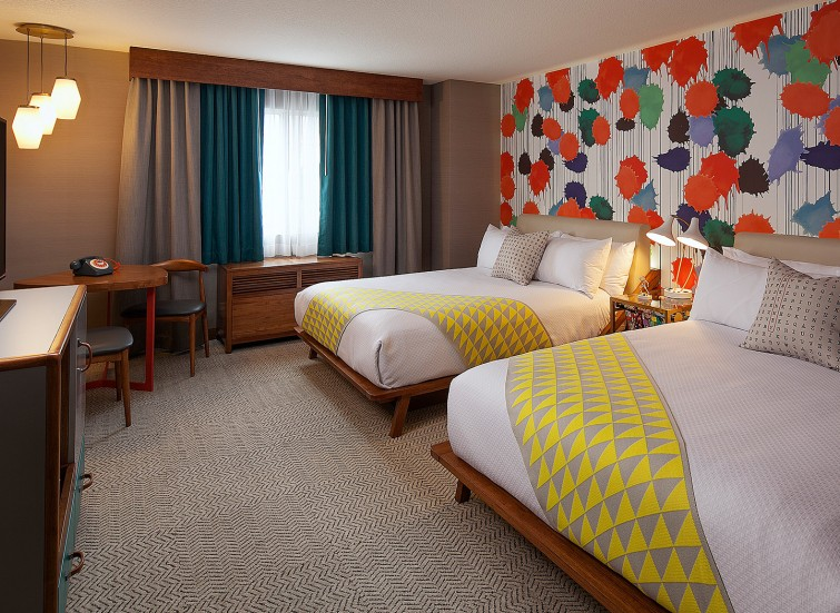 Hotel bedroom with 2 queen beds and a decorative paint splattered wall