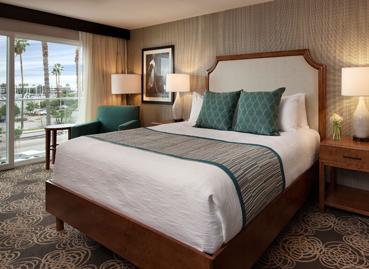 large bed with teal pillows and blanket with marina view