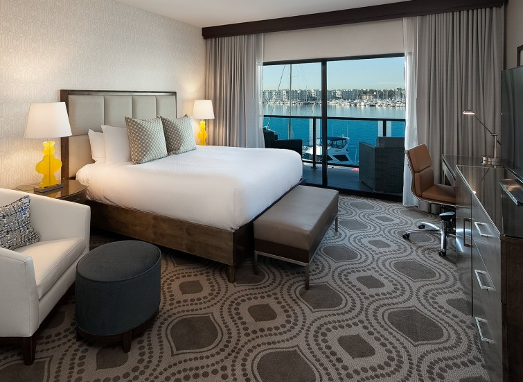 a guest suite with marina views and white bedding