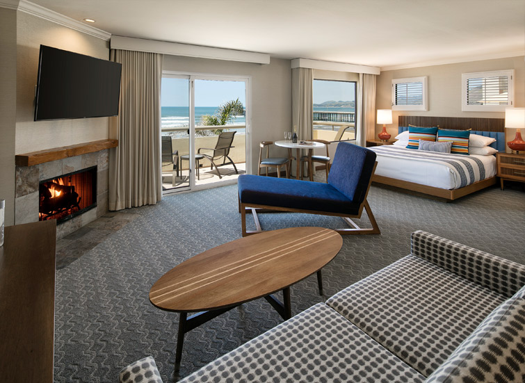 oceanfront suite with sitting room, bed and view of ocean