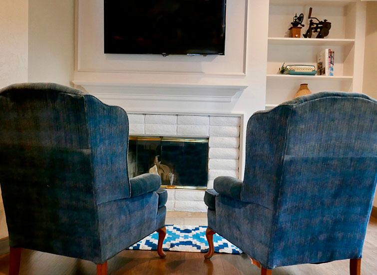two blue lounge chairs in front of a fire place